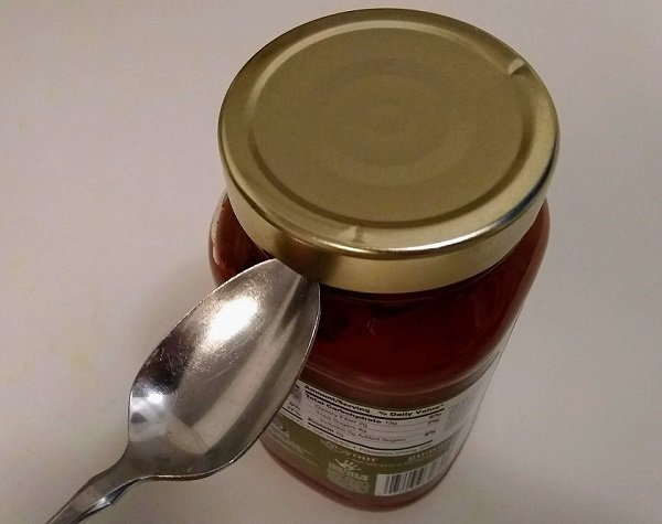 opening a jar lid by using a spoon